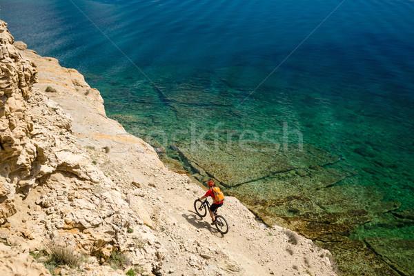 Mountain biker riding a bike on rocky trail path at sea Stock photo © blasbike