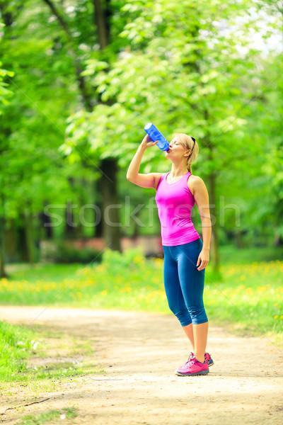 Woman runner drinking water on training Stock photo © blasbike