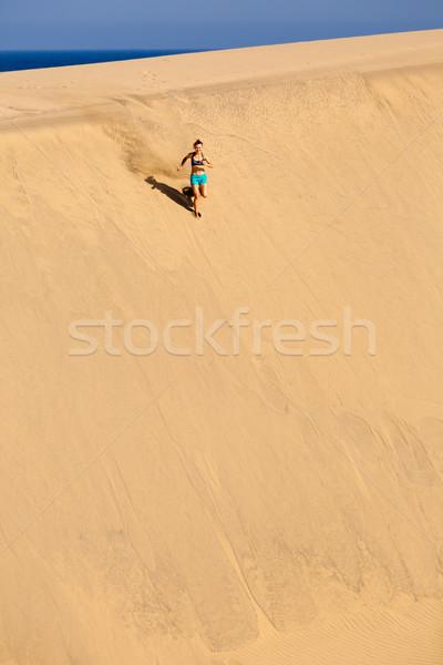 Athletic woman running on sand desert dunes Stock photo © blasbike