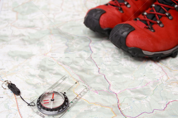 Hiking shoes and compass on map Stock photo © blasbike