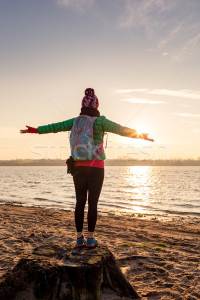 Woman hiker with arms outstretched enjoy sunrise at lake Stock photo © blasbike