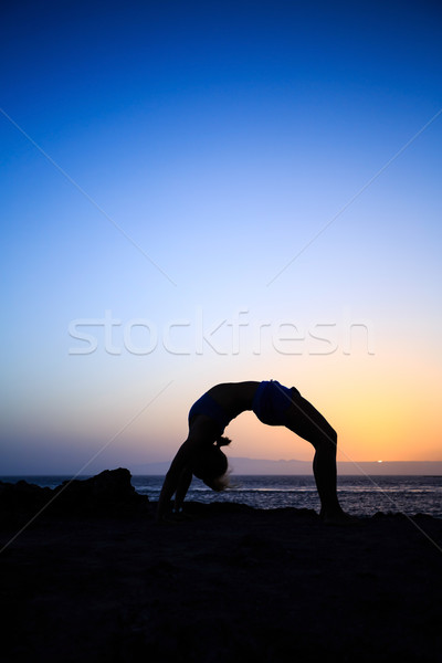 Woman stretches yoga sunset silhouette Stock photo © blasbike