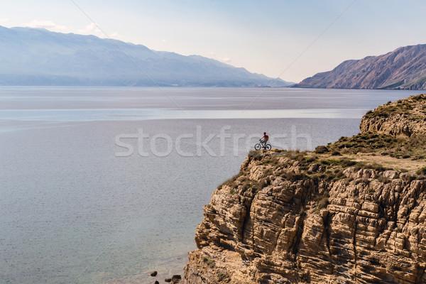 Mountain biker riding bike on rocks at the ocean Stock photo © blasbike
