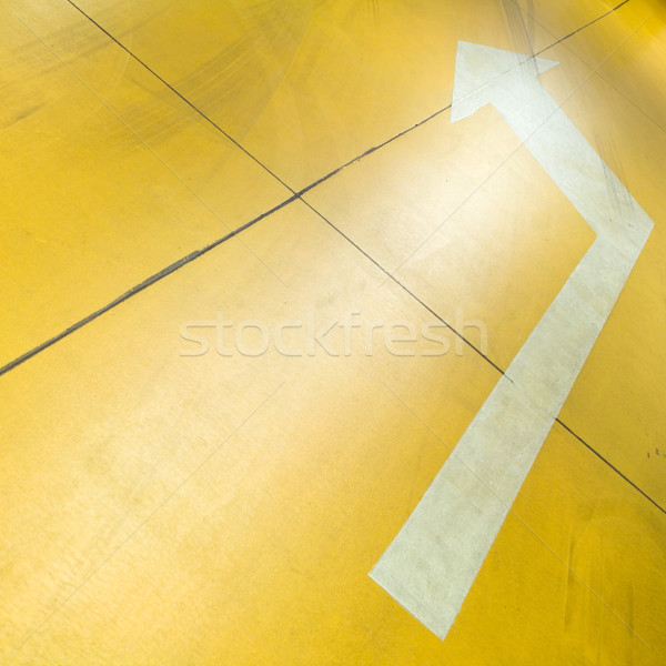 Stock photo: Arrow on yellow parking garage floor
