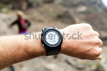 Stock photo: Hiker on mountain trail checking compass