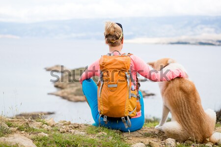 Woman hiker with dog looking at sea Stock photo © blasbike