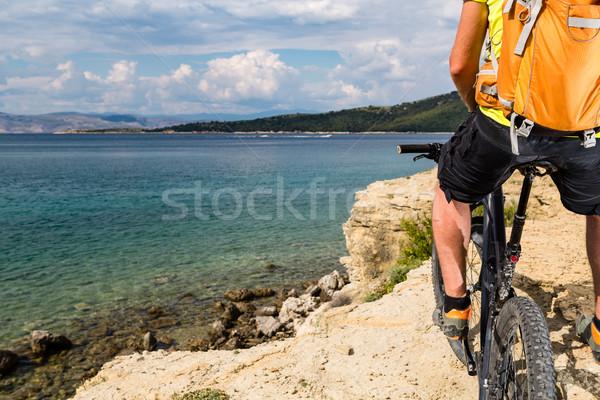 Mountain biker riding on bike at the sea and summer mountains Stock photo © blasbike