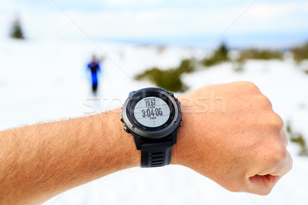 Runner on mountain winter trail looking at stopwatch, activity m Stock photo © blasbike