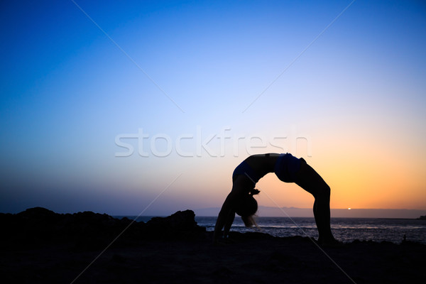 Stock photo: Woman stretches yoga sunset silhouette