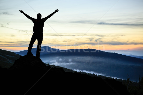 Man hiker successful with arms outstretched Stock photo © blasbike