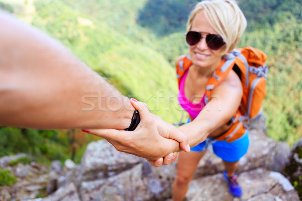 Man and woman helping hand in mountains Stock photo © blasbike