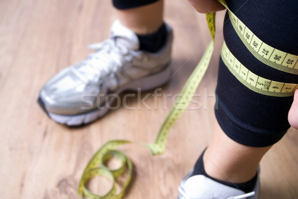 Woman measures a leg with centimeter after running at gym Stock photo © blasbike