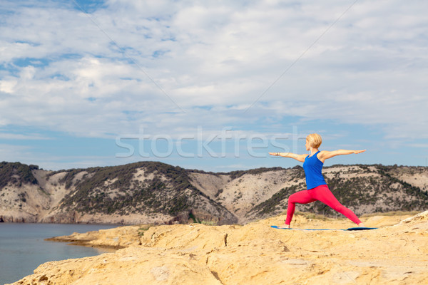 Woman meditating in yoga pose at the sea and mountains Stock photo © blasbike