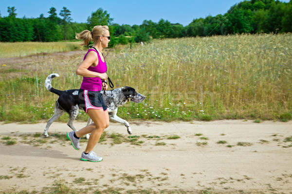Stock photo: Woman running and walking a dog