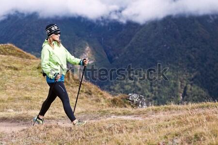 Woman hiker nordic walking in mountains Stock photo © blasbike