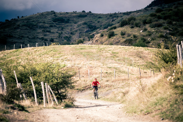 Mountain bike MTB rider on country road, track trail in inspirat Stock photo © blasbike