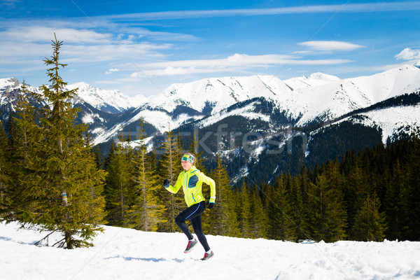 Happy woman running in mountains on winter snow Stock photo © blasbike