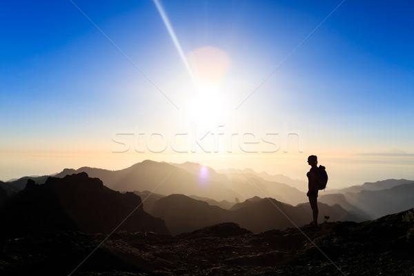 Mulher caminhadas sucesso silhueta montanhas pôr do sol Foto stock © blasbike