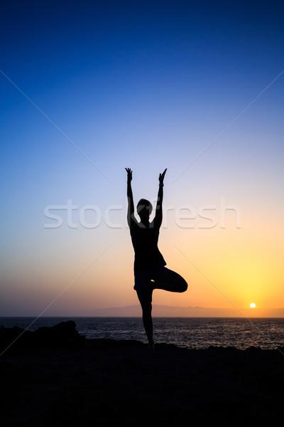 Woman exercising yoga sunset silhouette Stock photo © blasbike