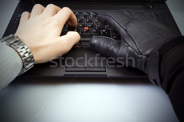 Businessman and hacker hands on laptop keyboard Stock photo © blasbike