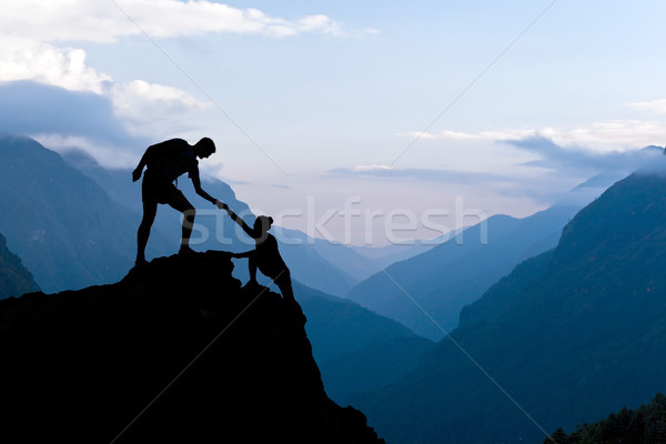 Teamwork couple climbing helping hand Stock photo © blasbike