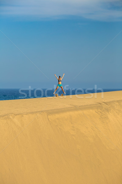Woman with arms up outstretched jumping on sand desert dunes Stock photo © blasbike
