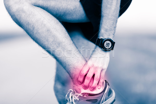 Leg ankle pain, man holding sore and painful foot Stock photo © blasbike