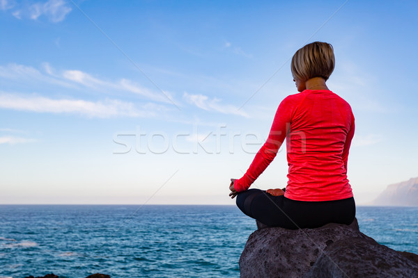 Woman meditating in yoga pose, ocean view Stock photo © blasbike