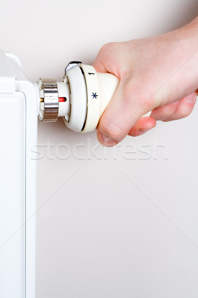 Men adjusting thermostat on home radiator Stock photo © blasbike