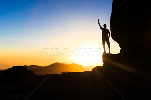 Man hiking climbing silhouette success in mountains sunset Stock photo © blasbike