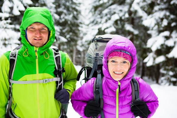 Couple happy hikers trekking in winter woods Stock photo © blasbike