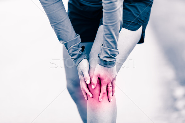 Knee pain, woman holding sore and painful leg Stock photo © blasbike