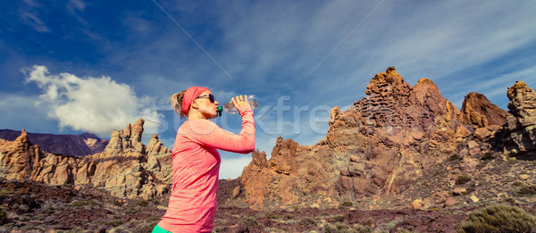 Woman trail runner drinking in inspiring mountains landscape Stock photo © blasbike