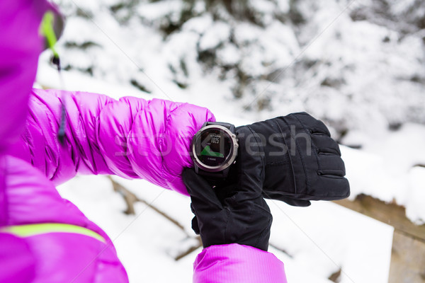 Woman hiker checking sports watch in winter woods and mountains Stock photo © blasbike