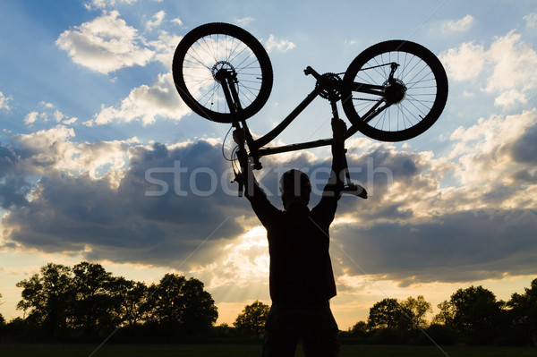 Cycling silhouette rider with bicycle holding up Stock photo © blasbike