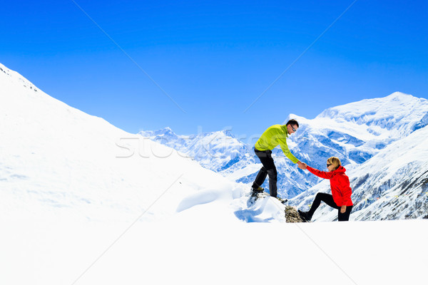Helping hand couple hikers in mountains Stock photo © blasbike