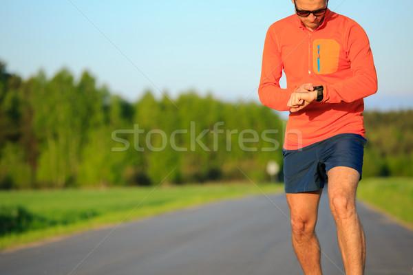 Runner training and checking stopwatch smart watch, cross countr Stock photo © blasbike