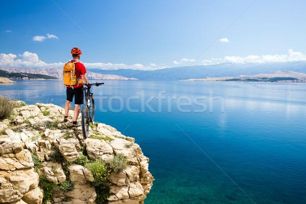 Mountain biking rider looking at inspiring sea and mountains Stock photo © blasbike