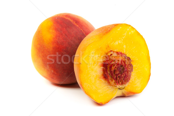 Three perfect, ripe peaches with a half  and slices isolated on  Stock photo © bloodua