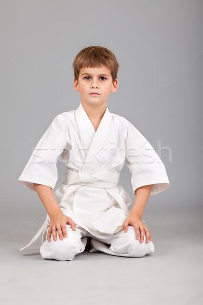 Karate fiú fehér kimonó ül izolált Stock fotó © bloodua
