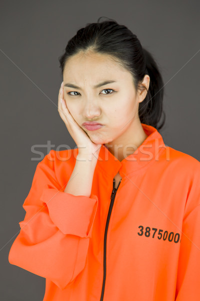Upset young Asian woman in prisoners uniform with her hands on cheek Stock photo © bmonteny