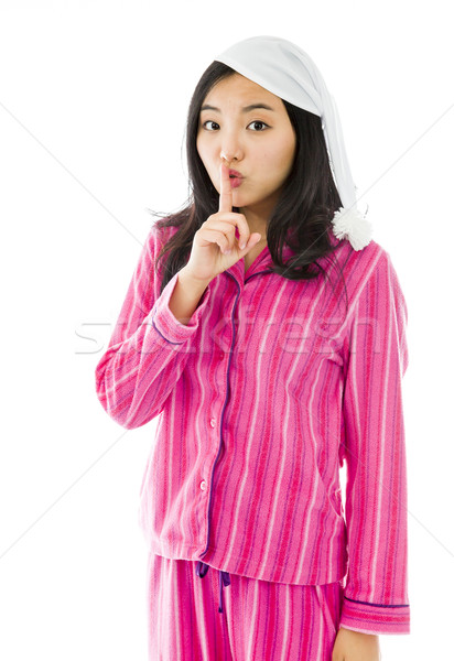 Stock photo: Young Asian woman standing with finger on lips