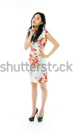 Stock photo: Asian young woman looking up with finger on chin isolated on white background
