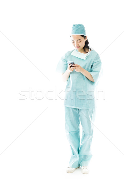 Asian female surgeon text messaging on a mobile phone Stock photo © bmonteny