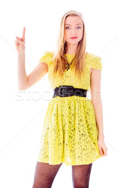 Beautiful young woman standing and pointing upward Stock photo © bmonteny