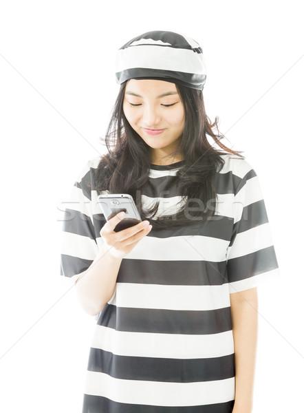 Fiatal ázsiai nő sms üzenetküldés mobiltelefon egyenruha Stock fotó © bmonteny