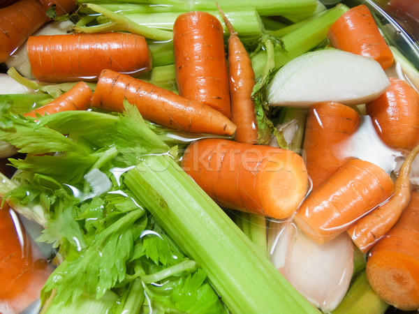 Pieces of carrot and spring onion in water Stock photo © bmonteny