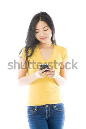 Stock photo: Angry young Asian woman shouting on a mobile phone