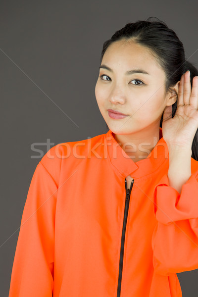 Nosy Young Asian woman trying to listen carefully isolated on white background Stock photo © bmonteny