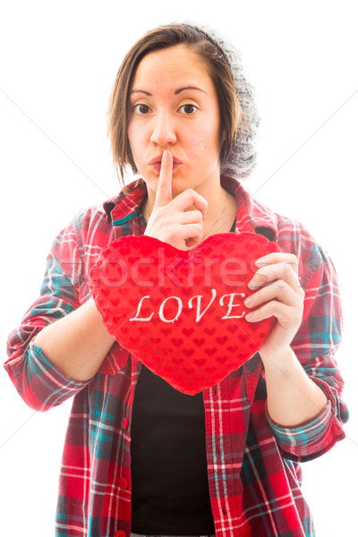 Young woman holding heart shape with a finger on lips Stock photo © bmonteny